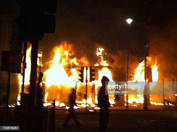 Carpetright store burns on Tottenham High Road after being set on fire by youths protesting against the killing of a man by armed police in an...