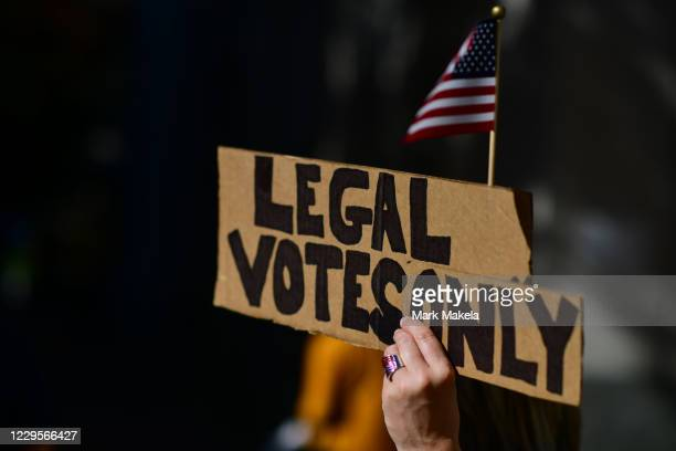 """Carri Dusza, a supporter of President Donald Trump, holds a sign that reads """"Legal Votes Only"""" while demonstrating outside of where votes are still..."""