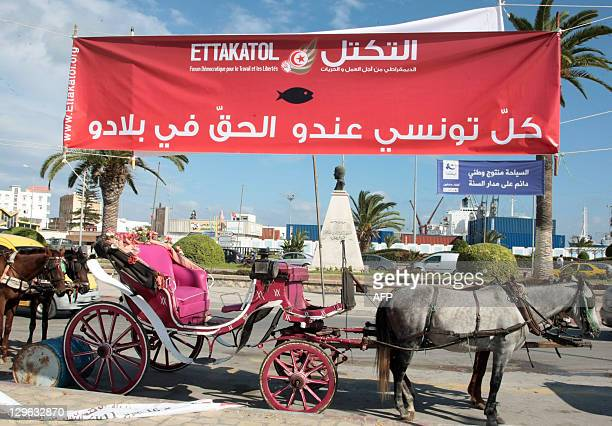 A carriage awaits tourists on October 19 2011 in Sousse under an electoral banner of the Ettakatol party For the town of Sousse known in tourist...