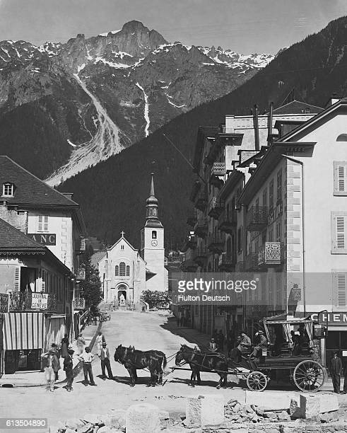 Carriage travelers pass through Chamonix at the foot of Mont Blanc in the French Alps   Location Chamoix France