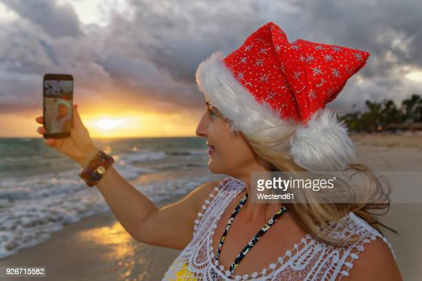 carribean, dominican republic, punta cana, woman with christmas cap taking selfie on the beach - caribbean christmas stock pictures, royalty-free photos & images