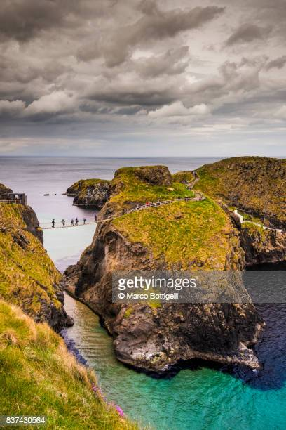 carrick-a-rede rope bridge, northern ireland. - northern ireland stock photos and pictures