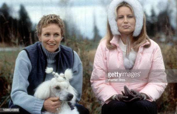 Carrie Aizley holding a dog next to Jennifer Coolidge in a scene from the film 'Best In Show' 2000