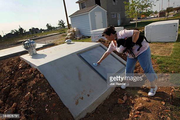 Carrie Cook shows off her newly built tornado shelter behind her Habitat for Humanity home in the heart of what was once nothing but debris and...