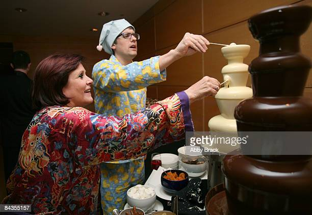 Carrie Fisher and Mo Rocca enjoy the chocolate fountain at the Obama Pajama Party at the Ronald Reagan Building on January 18 2009 in Washington DC...