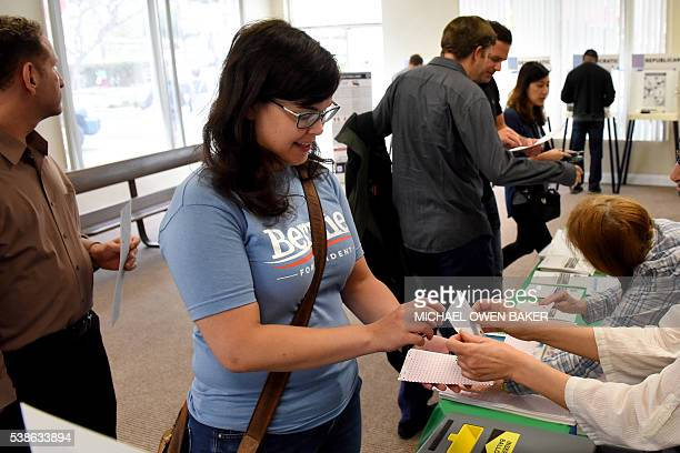 Carrie Frazier hands over her ballot after voting in the US presidential primary election June 7 2016 in West Hollywood California / AFP / Michael...