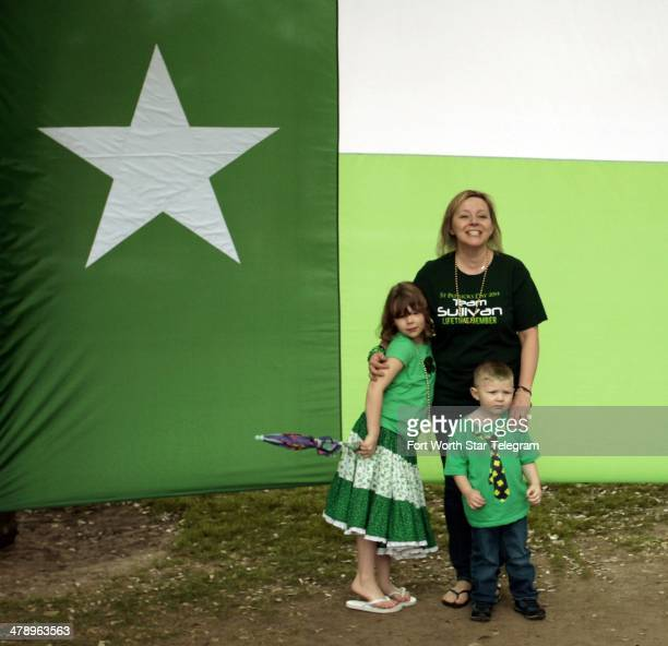 Carrie Johnston of Keller Texas poses with kids Mckaylaand Knox in front of a curiously green Lone Star flag at the Cowtown Goes Green event at the...