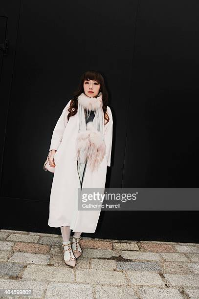 Carrie Kwok stylist and make up artist from Hong Kong wearing on trend head to toe pale dusky pink her look comprising a coat by Injury accessorising...