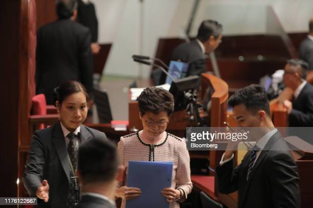 Carrie Lam, Hong Kong's chief executive, center, leaves the chamber of the Legislative Council after pro-democracy lawmakers disrupted her attempt to...