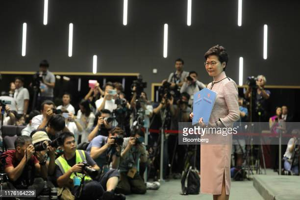 Carrie Lam, Hong Kong's chief executive, poses for photographs with copies of the policy address during a news conference in Hong Kong, China, on...