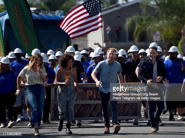Carrie Locklyn Breegan Jane Jesse Tyler Ferguson and Darren Keefe Reiher the cast of Extreme Makeover Home Edition march down the street to surprise...