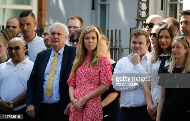 Carrie Symonds girlfriend of Britain's new Prime Minister Boris Johnson waits for the prime minister's arrival with members of staff in Downing...