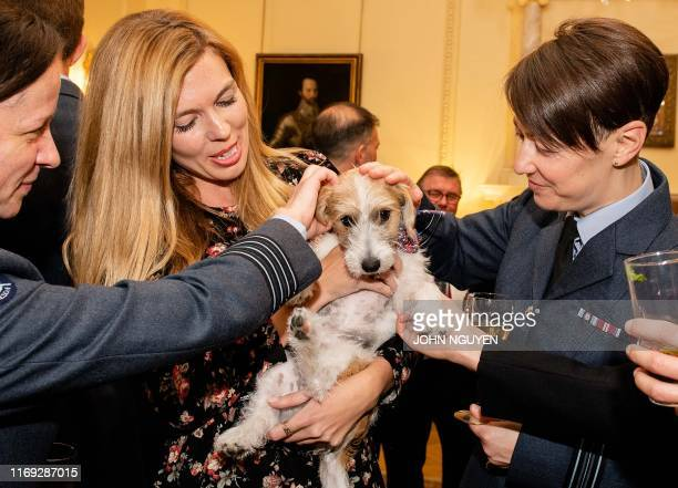 Carrie Symonds, girlfriend of Britain's Prime Minister Boris Johnson, holds their pet Jack Russell dog Dilyn, as she talks with members of Britain's...