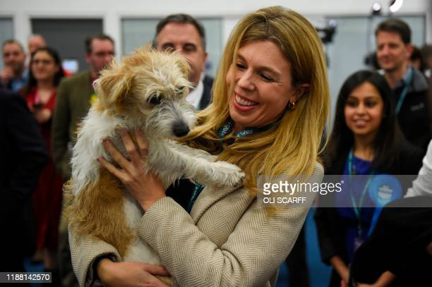 Carrie Symonds, partner of Britain's Prime Minister and Conservative leader Boris Johnson, holds their dog, a Jack Russell-cross named Dilyn, as she...