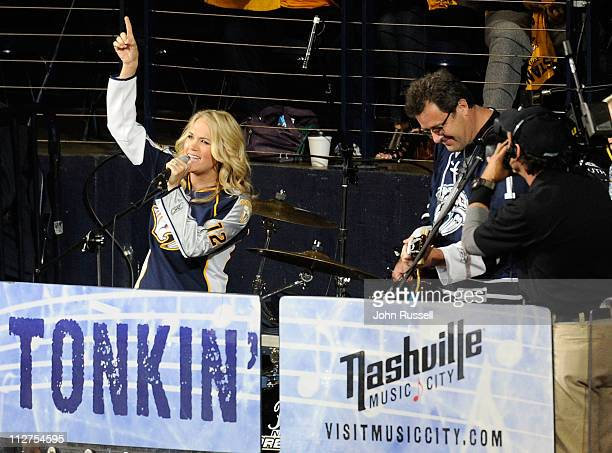Carrie Underwood performs with Vince Gill during the first intermission of the Nashville Predators and the Anaheim Ducks Game Four of the Western...