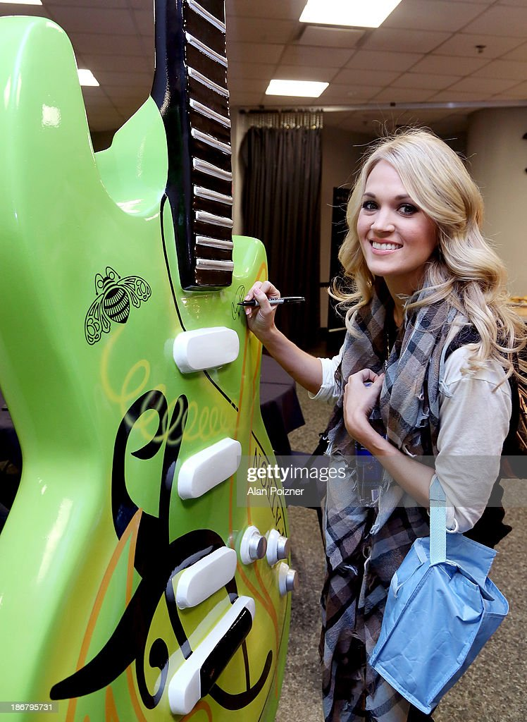 Carrie Underwood signs a giant Patron tequila guitar at the CMA Awards to benefit the 'Keep the Music Playing' music education on November 3, 2013 in Nashville, Tennessee.