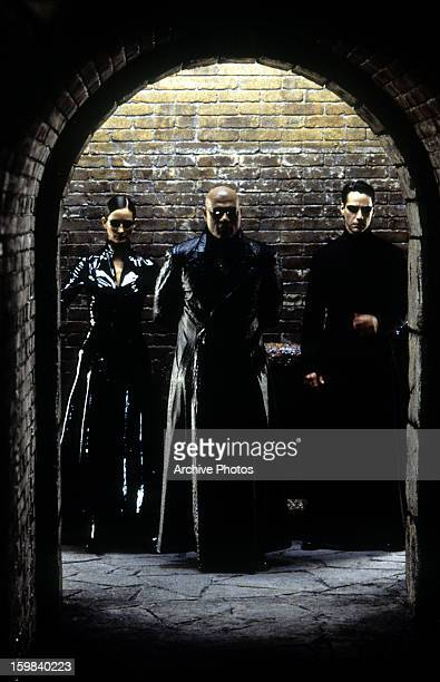 CarrieAnne Moss Laurence Fishburne and Keanu Reeves standing against brick wall in a scene from the film 'The Matrix Reloaded' 2003