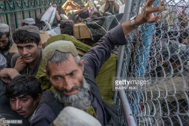 Carriers along with other people rush to pass the border gate to Pakistan from the Afghanistan border in Spin Boldak on September 25, 2021. -...