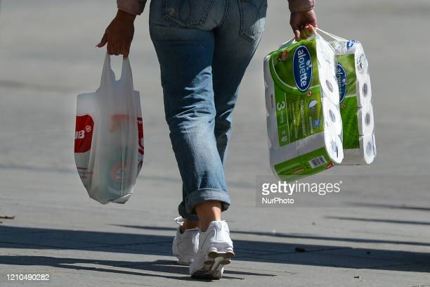 A carries shopping bag and toilet paper rolls in Krakow's Center From today the ban on moving traveling and staying in public places has been lifted...