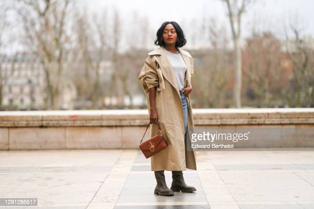Carrole Sagba aka Lianose wears a beige long trench coat from Nehera, a white t-shirt, blue jeans from Zara, a brown leather golden logo bag from JW...