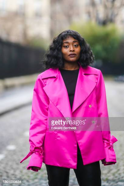 Carrole Sagba aka Linaose wears a neon pink blazer jacket with knot details on the sleeves/cuffs from Liya, a black t-shirt from Uniqlo, on February...