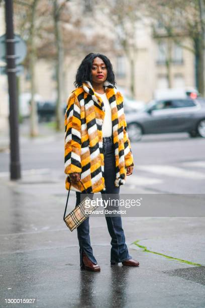 Carrole Sagba aka Linaose wears a yellow black and orange geometric pattern printed winter fluffy long coat from Apparis, black flared jeans from...