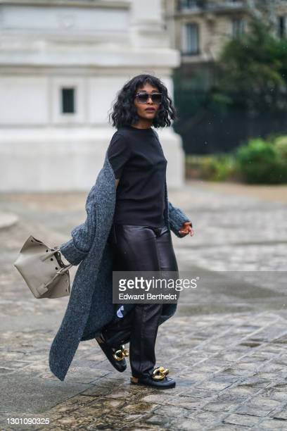 Carrole Sagba aka Linaose wears sunglasses, a black t-shirt from Uniqlo, a gray long wool cardigan from Zara, black leather pants, leather...