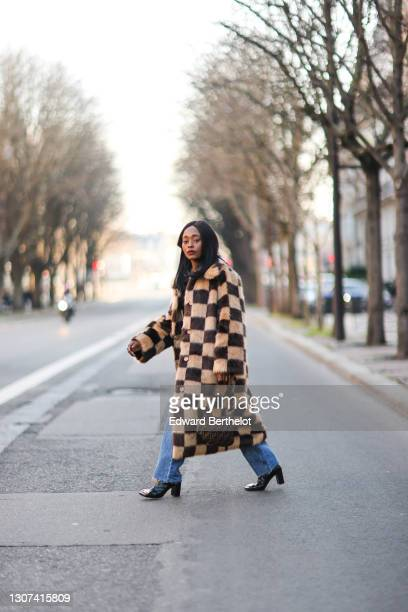 Carrole Sagba @linaose wears a beige and brown checked fluffy winter long coat from Stand Studio, a black top, blue jeans, a Fendi monogram bag,...