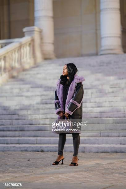 Carrole Sagba @linaose wears a black and purple leather long aviator coat with fluffy inner lining and a hood from Jakke, a burgundy leather Hermes...