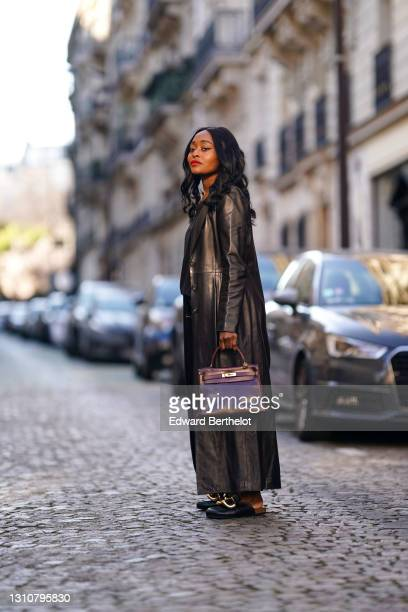 Carrole Sagba @linaose wears a black leather long trench coat from Mac Douglas, a black top from Calvin Klein, black denim jeans pants from Levi's,...