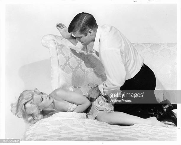 Carroll Baker getting manhandled by George Peppard in publicity portrait for the film 'The Carpetbaggers' 1964