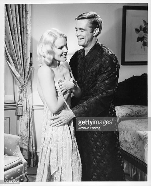 Carroll Baker is held by George Peppard in a scene from the film 'The Carpetbaggers' 1964