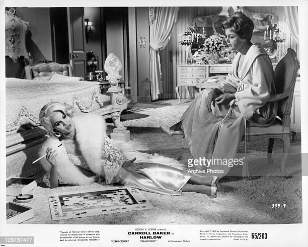 Carroll Baker on the floor talking to Angela Lansbury in a scene from the film 'Harlow' 1965