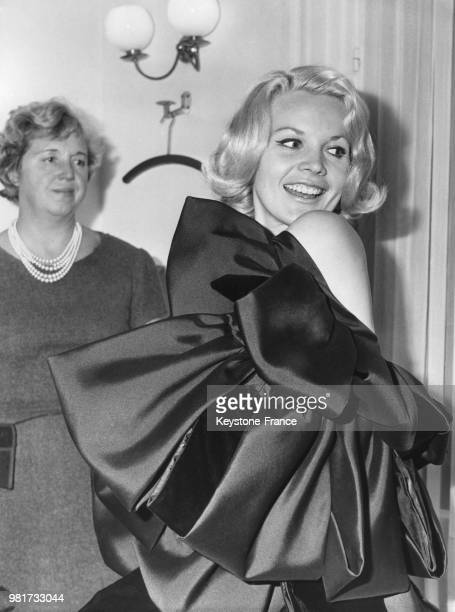 Carroll Baker porte la robe 'Milano' un fourreau en velours noir avec manteau cape orné de coques en zibeline noire et velours noir lors d'un...