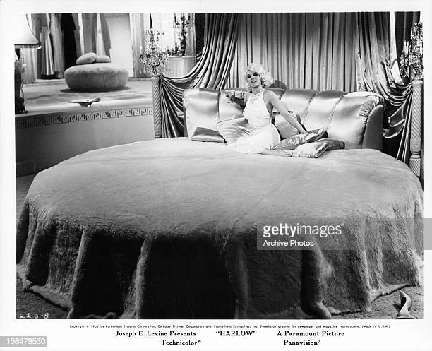 Carroll Baker sitting on a extra large round bed in a regal decorated bedroom in a scene from the film 'Harlow' 1966