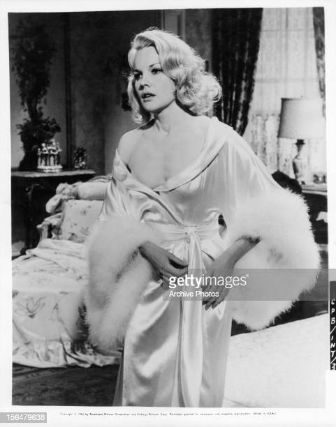 Carroll Baker standing in a bedroom wearing a silky robe with fur trim in a scene from the film 'Harlow' 1966