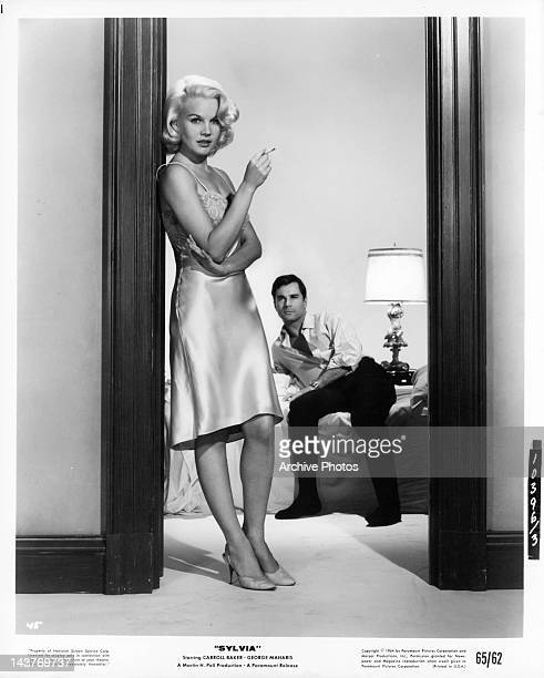 Carroll Baker standing in doorway with cigarette as George Maharis watches in a scene from the film 'Sylvia' 1964