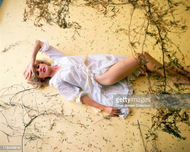 Carroll Baker US actress reclining against a yellow surface wearing a white night shirt surrounded by pieces of foliage in a studio portrait circa...