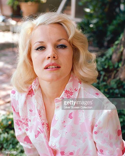 Carroll Baker US actress wearing a floral patterned pinkandwhite blouse circa 1965