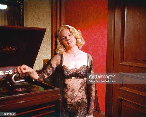 Carroll Baker US actress wearing a seethrough negligee revealing her black underwear beneath as she moves the stylus onto a record on a turntable...