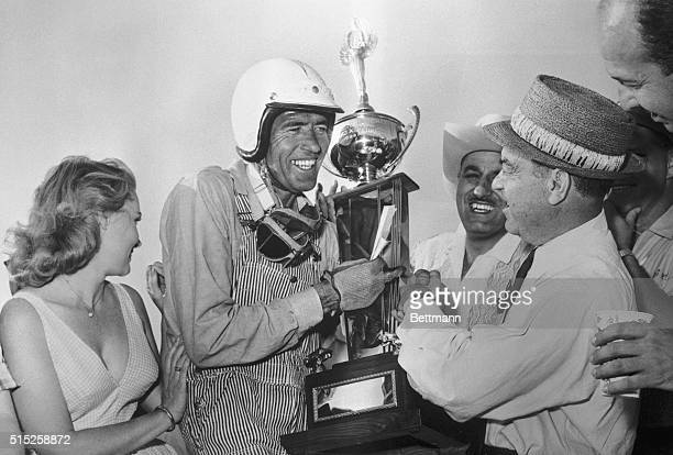 Carroll Shelby of Dallas Texas accepts trophy from Dave Brandman, executive director of racing, which Shelby won in the 20,000. Riverside GrandPrix...