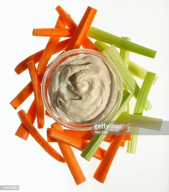Carrot and celery sticks and bowl of hummus dip