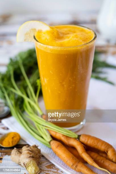 carrot and ginger smoothie - brycia james stock pictures, royalty-free photos & images
