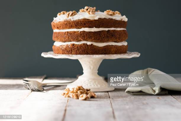 carrot cake on a cake stand with cream cheese frosting - carrot cake stock pictures, royalty-free photos & images