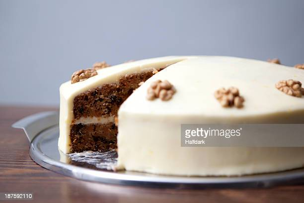 A carrot cake with a slice missing for sale in a cafe