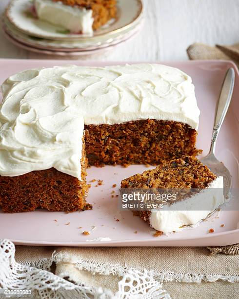carrot cake with frosted icing on pink dish - carrot cake stock pictures, royalty-free photos & images