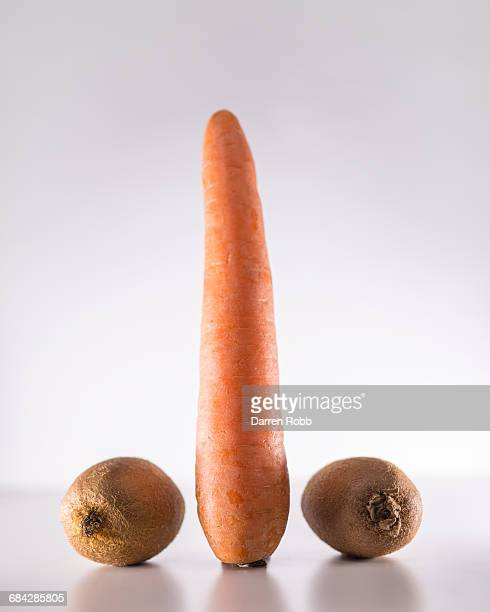 a carrot inbetween two kiwi fruits - erectile dysfunction stock pictures, royalty-free photos & images