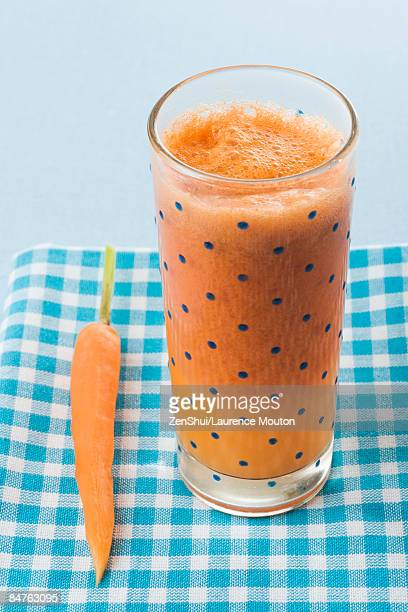 Carrot juice beside a single carrot on tablecloth