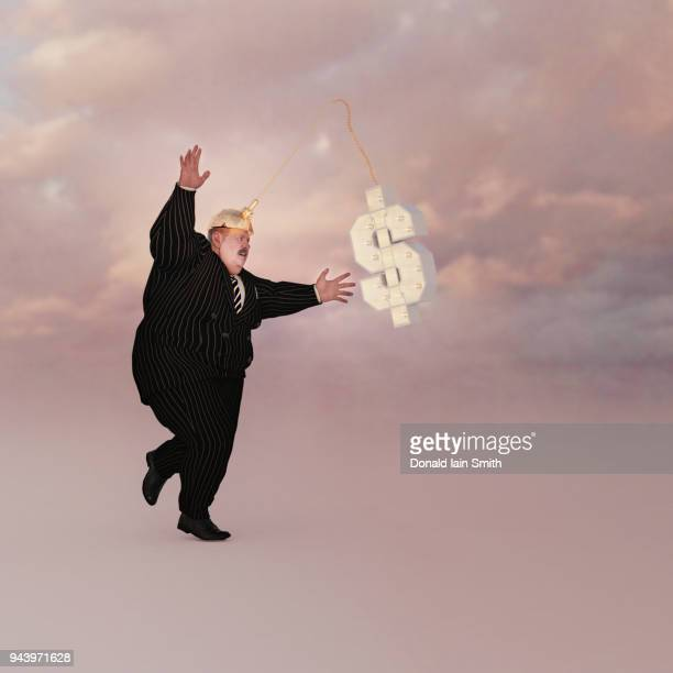 carrot on a stick concept for business man using dollar on a stick. - greedy smith stock pictures, royalty-free photos & images