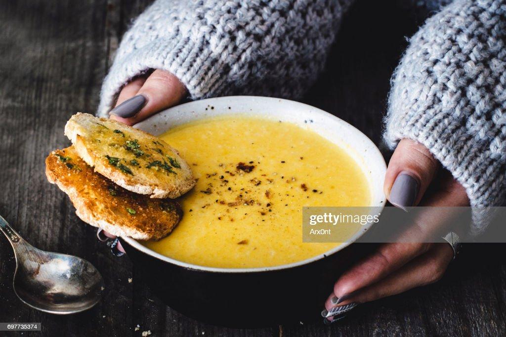 Carrot pumpkin cream soup with garlic bread : Stock Photo